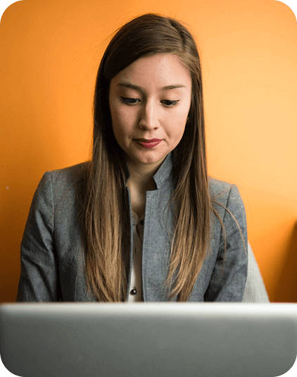 Woman learning using laptop with orange background